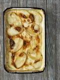 Rustic golden scalloped potato gratin dauphinois Stock Photos