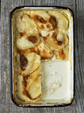 Rustic golden scalloped potato gratin dauphinois Stock Images