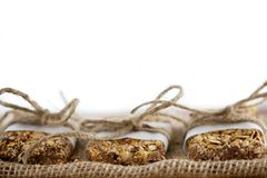 Rustic Granola Bars wrapped with Twine on Burlap White BG Stock Photos