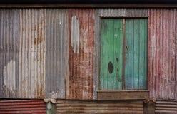 Rustic green door background. Rustic green wooden door in rusty textured corrugated iron wall Stock Photos