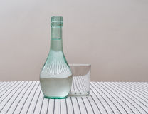Rustic green glss carafe of water with drinking glass on striped Royalty Free Stock Image