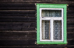 Rustic green painted wood frame window. Old green and white painted wood frame window with lace curtains in dark wood exterior wall Stock Images