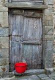 Rustic grey door and red bucket. Stock Photos