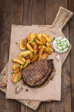 Rustic grilled beefsteak with french fries stock photography