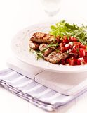 Rustic grilled pork tenderloin with tomato salsa. On wooden chopping board. Vertical royalty free stock photo