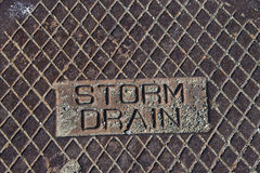 Rustic grunge storm drain manhole cover close up on storm drain Royalty Free Stock Images