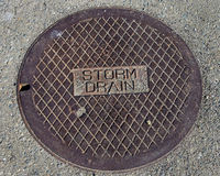 Rustic grunge storm drain manhole cover in concrete. Rustic grunge storm drain manhole cover in rock filled concrete walkway Stock Photography