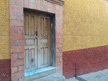 Rustic Hand-Carved Antique Wooden Door in Primitive Textured Mexican Brick and Stucco Wall with Gold, Rust, Blue Background Colors Stock Photo