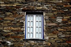 Rustic hand-hewn wood window set into a stone wall built from schist in Piodão, made of shale rocks stack, one of Portugal's. Schist villages in the Aldeias stock image