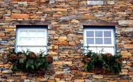 Rustic hand-hewn wood window set into a stone wall built from schist in Piodão, made of shale rocks stack, one of Portugal's. Schist villages in the Aldeias royalty free stock photo