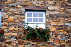 Rustic hand-hewn wood window set into a stone wall built from schist in Piodão, made of shale rocks stack, one of Portugal's. Schist villages in the Aldeias royalty free stock images