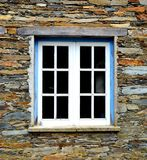 Rustic hand-hewn wood window set into a stone wall built from schist in Piodão, made of shale rocks stack, one of Portugal's. Schist villages in the Aldeias stock photos