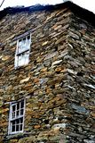 Rustic hand-hewn wood window set into a stone wall built from schist in Piodão, made of shale rocks stack, one of Portugal's. Schist villages in the Aldeias stock photo
