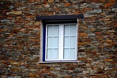 Rustic hand-hewn wood window set into a stone wall built from schist in Piodão, made of shale rocks stack, one of Portugal's. Schist villages in the Aldeias stock photography