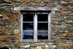 Rustic hand-hewn wood window set into a stone wall built from schist in Piodão, made of shale rocks stack, one of Portugal's. Schist villages in the Aldeias royalty free stock image