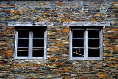 Rustic hand-hewn wood window set into a stone wall built from schist in Piodão, made of shale rocks stack, one of Portugal's. Schist villages in the Aldeias royalty free stock photos