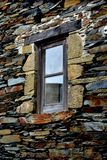 Rustic hand-hewn wood window set into a stone wall built from schist in Piodão, made of shale rocks stack, one of Portugal's. Schist villages in the Aldeias do stock photo