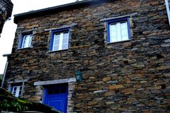 Rustic hand-hewn wood window set into a stone wall built from schist in Piodão, made of shale rocks stack, one of Portugal's. Schist villages in the Aldeias stock images