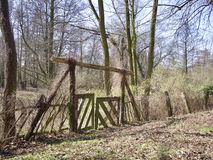 Rustic handmade wooden gate leading to woodland. Rustic handmade wooden fence with closed double gates leading to woodland with leafless winter or autumn trees Royalty Free Stock Photo