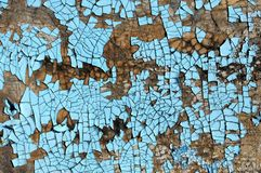 Rustic hardboard texture with scratches, cracks and blue peeling paint. Grunge background Royalty Free Stock Image