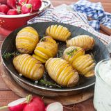 Rustic hasselback potatoes. With fresh thyme and sea salt Royalty Free Stock Photography