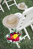 Rustic hat and flower bouquet in rural garden scene. On sunny summer day stock images