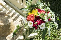 Rustic hat and flower bouquet in rural garden scene. On sunny summer day royalty free stock images