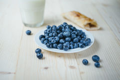 Rustic healthy breakfast with blueberry, small loaf and milk in a glass on a wooden table. Glass of milk with ripe berries. Health Royalty Free Stock Photos