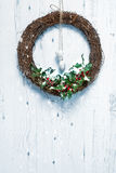 Rustic Holiday Garland. Rustic Christmas garland decorated with holly and berries hanging on white door Stock Photo