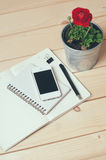 Rustic home office. Rustic tabletop, home office: notebooks, smart phone, pen and a flower Royalty Free Stock Photography