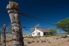 Rustic home surrounded by barbed wire Stock Photos
