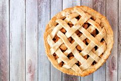 Homemade apple pie with lattice pastry over aged wood. Rustic homemade apple pie with lattice pastry, above view on aged wood Stock Images