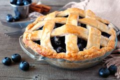Rustic homemade blueberry pie, close up scene on rustic wood. Rustic homemade blueberry pie with lattice pastry. Close up scene on a rustic wooden background stock image
