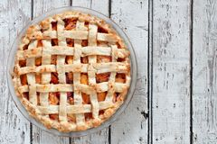 Rustic homemade peach pie, above view on aged white wood Royalty Free Stock Images