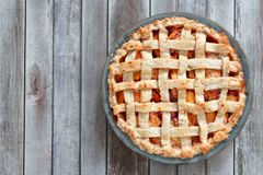 Rustic homemade peach pie, above view on wood Stock Images