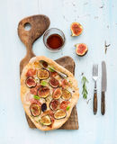 Rustic homemade pizza with figs, prosciutto and mozzarella cheese on dark wooden serving board over light blue backdrop Stock Photo