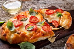 Rustic Homemade Pizza Margherita. A delicious rustic homemade pizza margherita with fresh mozzarella cheese, roma tomatoes and basil royalty free stock image