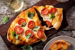 Rustic Homemade Pizza Margherita. A delicious rustic homemade pizza margherita with fresh mozzarella cheese, roma tomatoes and basil stock photography