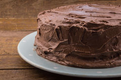Rustic homemade whole chocolate cake on wood table. Rustic homemade whole frosted chocolate cake on wood table Royalty Free Stock Photography