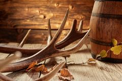 Rustic house decoration of antler and barrel. Rustic hunter house or bar decoration of deer antler, autumn yellow leaves and wooden barrel on the surface of old stock photos