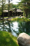 Rustic house by pond Royalty Free Stock Images
