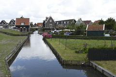 Rustic houses along a canal in Marken, Netherlands. The typical dark houses with red tile roofs line a canal in the Dutch town of Marken Stock Images