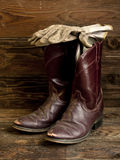 Rustic image of boots and gloves. A concept image of worn cowboy boots and gloves royalty free stock images