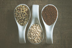 Rustic image of mixed grains in white spoons on wood Stock Image