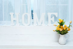 Rustic interior decor. Word Home on windowsill with white jug full of yellow tulips. Rustic interior decor. Word Home on windowsill with white jug full of Royalty Free Stock Photos