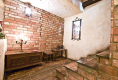 Rustic interior stairs. Interior of a rustic country house, stairs at the right, red brick wall and old furniture lined up at the wall Royalty Free Stock Photography