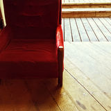 Rustic interior with vintage red velvet armchair Stock Images