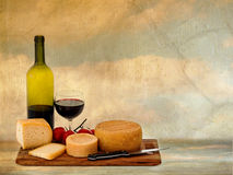 Rustic Italian artisan cheese with red wine and tomatoes. Royalty Free Stock Photography