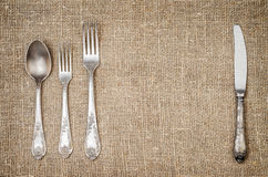 Rustic jute background with vintage silver tableware Royalty Free Stock Photography