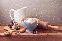 Rustic kitchen background with eggs and heart cookie cutters. Stock Photos